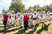 MONTVALE, NJ - October 3: The Crusaders arrive to their first road game at rival St. Jospehs high school ready to start their season. <br /> <br /> Coach Vito leads his team on the long walk from their changing tent area to the field.<br /> <br /> We are in the midst of witnessing something this world has never experienced - a global pandemic. The coronavirus has swept away the world in March of 2020 - since then, the world we know It hasn't been the same. Jobs, businesses and futures have been put on hold and lost, yet, we have to power through to overcome one of the greatest obstacles this we have faced. The high school football season wasn't suppose to happen, but a glimmer of hope, intense safety measures & a little bit of luck has allowed for the season to start, now the question is ' Can It be completed?'<br /> <br /> Photo by Johnnie Izquierdo