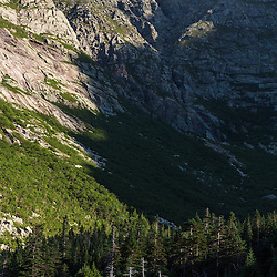 A hiker is dwarfed by the headwall on Mount Katahdin above Chimney Pond in Maine's Baxte State Park.