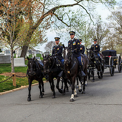 Arlington, VA - April 11, 2013: US Army soldiers ride on horses pulling a caisson through the military cemetery.