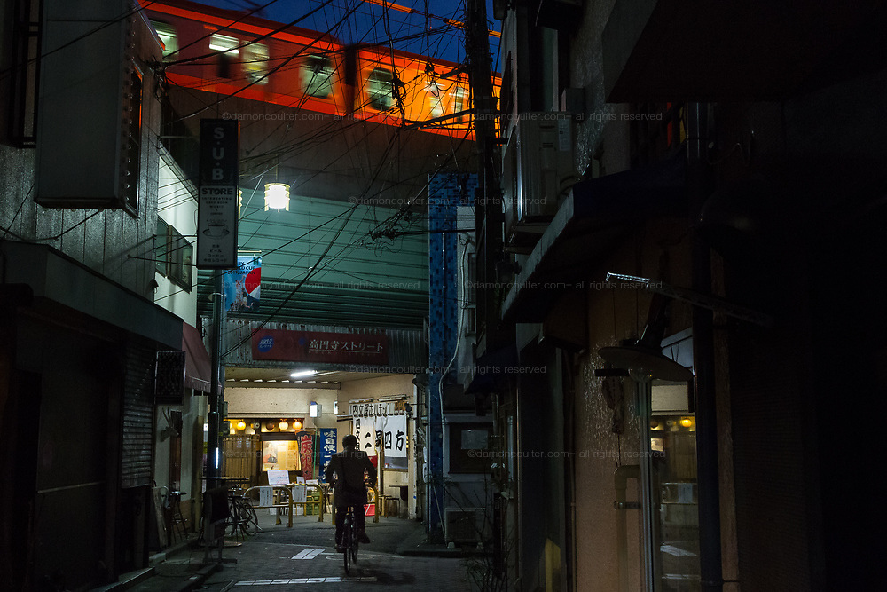 A train illuminated by a sign crosses a bridge above Koenji Street, shopping arcade  in the backstreets of Koenji, Tokyo, Japan. Wednesday October 30th 2019