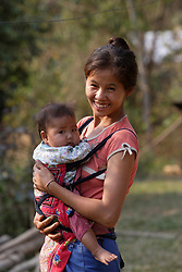 Juneng with her child Amai at tap stand. SCI has installed a gravity flow water system here. This village is in two parts with two communities, with lowland Lao on one side and Hmong on the other side. Naluang Village, Nambac District, Luang Prabang Province. Lao PDR