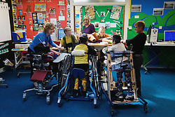 Children with learning and physical disabilities learning using supporting chairs in a lesson,