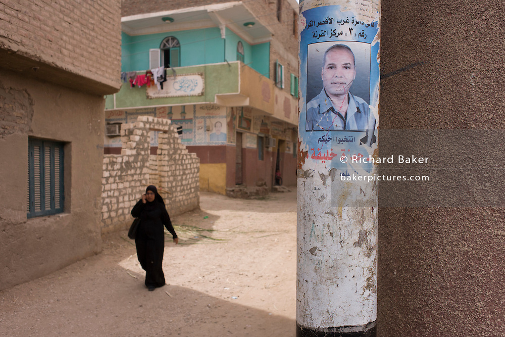 A local woman walks through Qurna, a village on the West Bank of Nile Valley, Egypt where a local teacher and congressman, Ahmed Hamza, appears on regional election posters.