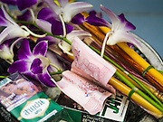 "23 MARCH 2013 - NAKHON CHAI SI, NAKHON PATHOM, THAILAND:  A 100 Baht note (about $3.30 US), orchids and cigarettes donated to a monk for a Sak Yant tattoo at Wat Bang Phra. Wat Bang Phra is the best known ""Sak Yant"" tattoo temple in Thailand. It's located in Nakhon Pathom province, about 40 miles from Bangkok. The tattoos are given with hollow stainless steel needles and are thought to possess magical powers of protection. The tattoos, which are given by Buddhist monks, are popular with soldiers, policeman and gangsters, people who generally live in harm's way. The tattoo must be activated to remain powerful and the annual Wai Khru Ceremony (tattoo festival) at the temple draws thousands of devotees who come to the temple to activate or renew the tattoos. People go into trance like states and then assume the personality of their tattoo, so people with tiger tattoos assume the personality of a tiger, people with monkey tattoos take on the personality of a monkey and so on. In recent years the tattoo festival has become popular with tourists who make the trip to Nakorn Pathom province to see a side of ""exotic"" Thailand. The 2013 tattoo festival was on March 23.  PHOTO BY JACK KURTZ"