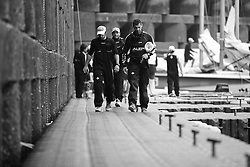 Team Aleph crew members make their way up the dock after finishing their round robin matches. Korea Match Cup 2010. World match Racing Tour. Gyeonggi, Korea. 12 June 2010. Photo: Gareth Cooke/Subzero Images