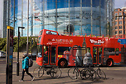 A tour bus drives beneath a large advert for American Airlines of a wide-bodied airliner in Waterloo, south London. As a pedestrian walks past, we see images of the capital's famous landmarks including The Millennium Wheel, the Gherkin, St Paul's and Tower Bridge, are seen on the side of the bus. Above is a large billboard advertising American Airlines, their wide-bodied airliner seemingly flying across the landscape.