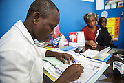 A nurse writes prescriptions for Lusseini (left) and Lacine, both 4 and suffering from malaria and diarrhea, to give their mother Katy Cherif, 40, during a consultation at the Libreville health center in Man, Cote d'Ivoire on Wednesday July 24, 2013.