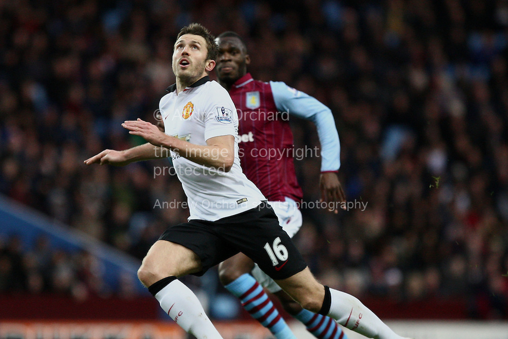 Michael Carrick of Manchester United reads the flight of the ball, under pressure from Christian Benteke of Aston Villa. Barclays Premier league match, Aston Villa v Manchester Utd at Villa Park in Birmingham on Saturday 20th December 2014<br /> pic by Mark Hawkins, Andrew Orchard sports photography.