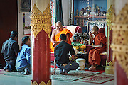 Inside the Dhammikarama Burmese Buddhist Temple men meet with the clergy. Located on Penang, Malaysia.