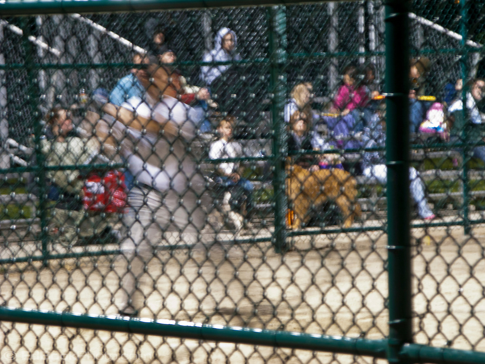 A long exposure motion blurs a baseball batter starting his swing seen through the diamond-shaped grid of the backstop.
