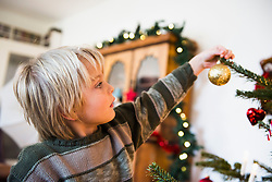 Little boy decorating Christmas tree at home