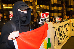 "London, October 25th 2014. Dozens of Britain's Kurdish community and their supporters demonstrated outside the exclusive Savoy as Turkey's ambassador welcomed guests to a ball. The Kurds accuse Turkey of helping Jihadists from ISIS in eradicating Kurds, who have held a long campaign for an autonomous Kurdish state. Pictured: A masked protester supports a banner reading ""Turkey! Stop supporting ISIS"""