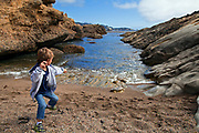 Young boy skipping stones at Point Lobos State Reserve, Monterey County, California, USA (MR)