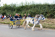 A man and boy drive a white horse and yellow wagon towards the flash, a strip of dirt road where people show off their horses at Appleby Horse Fair, the biggest gathering of Gypsies and travellers in Europe, on 14th August, 2021 in Appleby, United Kingdom. Appleby Horse Fair attracts thousands from Gypsy, Romany, and traveller communities annually, making it the biggest gathering of its kind in Europe. Generally held for a week every June, the fair was postponed in 2020 and pushed forward to August in 2021 due to Coronavirus.