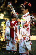 """Two girls hold bags of """"thousand year sweets"""", long pieces of candy symbolising longevity, which have been given to them at their shichi-go-san, in Tokyo, Japan. During shichi-go-san, literally seven-five-three, parents dress their daughters aged three and seven and sons aged five in traditional costume and take them to a Shinto shrine to be blessed."""