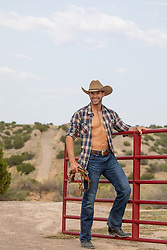 hot masculine cowboy with open shirt outdoors on a ranch