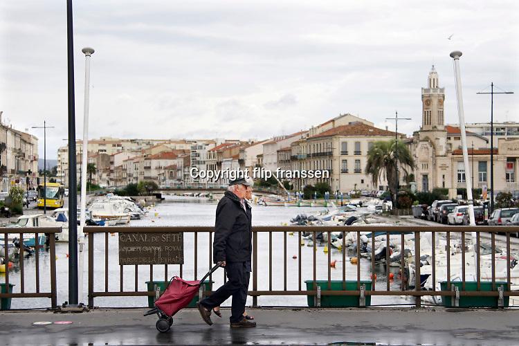 Frankrijk, Sete, 3-11-2019Ouder echtpaar loopt over een brug van het kanaal wat naar de zee leidt . Ze hebben een trolley bij zich om boodschappen in te vervoeren . Foto: Flip Franssen