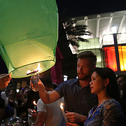 Members of the crowd light a floating lantern during a vigil at the Dr. Phillips Center for the Performing Arts for the victims of a mass shooting at the Pulse nightclub Monday, June 13, 2016, in Orlando, Florida.  A gunman killed dozens of people in a massacre at the crowded gay nightclub in Orlando on Sunday, making it the deadliest mass shooting in modern U.S. history. (Alex Menendez via AP)