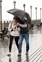 © Licensed to London News Pictures.09/04/2012, Skegness, North Lincolnshire, UK. Bank Holiday Monday weather, Skegness sea front.Pictured, a young couple shelter from the winds on Skegness pier. Photo credit : Dave Warren/LNP