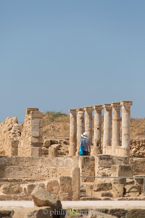 Female tourist exploring ancient ruins with columns, Paphos Archaeological Park, Paphos, Cyprus