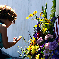 """A family member of Lorraine G. Bay a passenger on United Flight 93 places a caterpillar on the flowers at the """"Wall of Names""""  at the Flight 93 National Memorial near Shanksville, Pa.,  on the 14th observance of the Flight 93 crash and Sept. 11 terrorist attacks. Photo by Archie Carpenter/UPI ."""