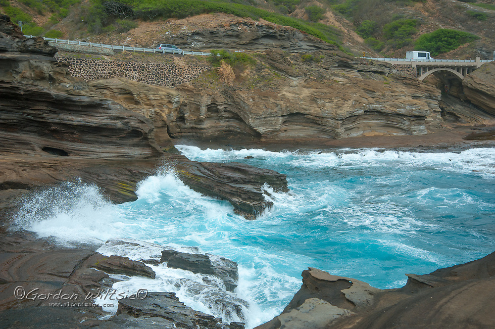 Pacific Ocean waves crash onto eroded sandstone cliffs on the southeast shore of Oahu, Hawaii. The Kamehameha Hightway runs in the background.