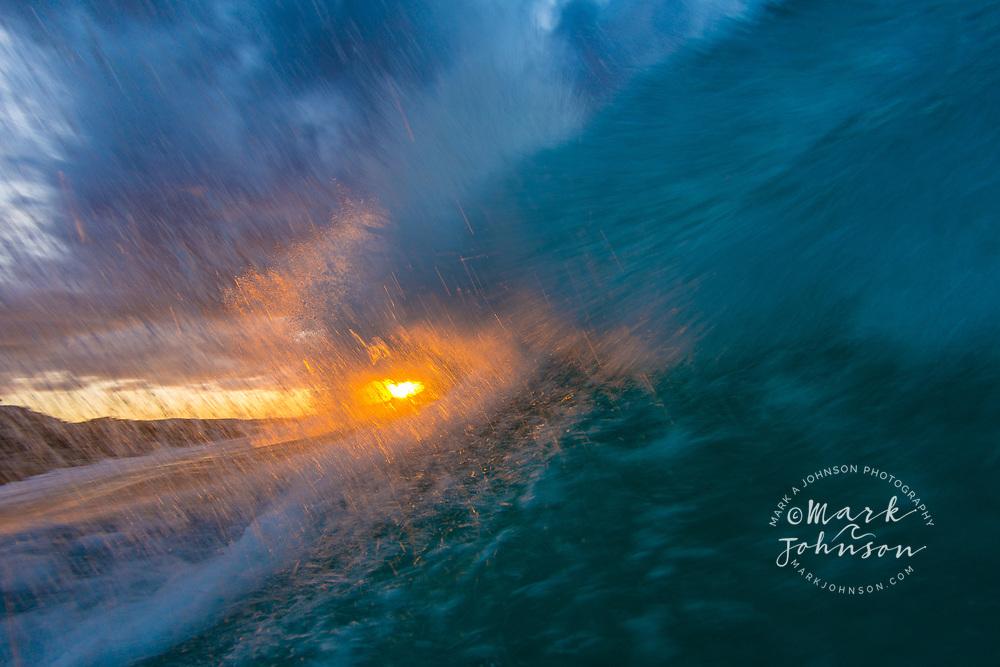 Sunset backlights a beautiful wave off the Queensland coast, Australia