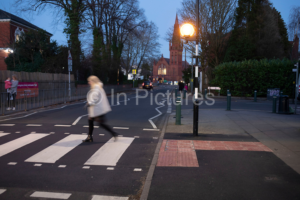 Pedestrian crossing at night in Kings Heath on 6th Febuary 2020 in Birmingham, United Kingdom. A zebra crossing is a type of pedestrian crossing used in many places around the world. Its distinguishing feature is alternating dark and light stripes on the road surface, resembling the coat of a zebra. A zebra crossing typically gives priority to pedestrians.