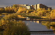 Photo: Randy Vanderveen.Grande Prairie, Alberta.A pedestrian crosses a bridge over Bear Creek on a beautiful fall morning while the colours of fall and GPRC provide a backdrop. Grande Prairie Regional College was designed by the world-renown Canadian architect Douglas J. Cardinal.
