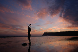 © Licensed to London News Pictures. <br /> 08/10/2014. <br /> <br /> Saltburn, United Kingdom<br /> <br /> Surfer Sam Davies stretches before going for an early morning surf as the sky is dramatically lit up at dawn on Saltburn beach in Cleveland.<br /> <br /> Photo credit : Ian Forsyth/LNP