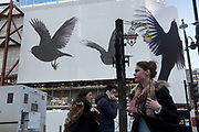 People pass a hoarding decorated with pictures of Blackbirds on a construction site in central London, UK.