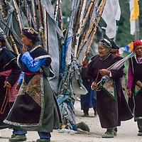 CHINA, TIBET.  Village women circumambulate a Tibetan Buddhist chorten & prayer flags during a small-town festival west of Nyingchi.
