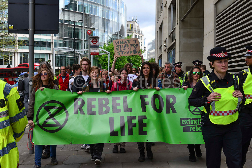 Climate change activists from the Extinction Rebellion group march and sing songs close to St Pauls tube station demanding that the British Government acknowledge the climate crisis posed by global warming on 25th April 2019 in London, England, United Kingdom.