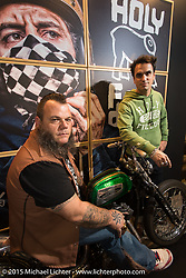 Benzina Alessio Ugolotti (seated) with Fede Maggi in the Holy Freedom display booth with a custom Ironhead Harley-Davidson Sportster during EICMA, the largest international motorcycle exhibition in the world. Milan, Italy. November 21, 2015.  Photography ©2015 Michael Lichter.