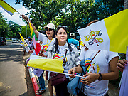 27 NOVEMBER 2017 - YANGON, MYANMAR: Women with Myanmar and Vatican flags cheer as Pope Francis and his motorcade pass them on the route into Yangon. Pope Francis arrived in Yangon Monday for a four day / three night visit. Tuesday he is going to the capitol, Naypyidaw (Nay Pyi Taw) to meet with Aung San Suu Kyi and other Myanmar leaders. Wednesday and Thursday he is saying mass in Yangon and on Thursday afternoon he is going to neighboring Bangladesh. There are around 450,000 Catholics in Burma, about 1% of the total population.   PHOTO BY JACK KURTZ