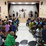 """Matt Golden '20 of New Bedford, Mass., perform a high jump center stage while performing with Bates students in Gretchen Berg's short term course """"Teach, Tour, Perform"""" while performing for McMahon Elementary School third graders on May 24, 2018. """"Teach, Tour, Perform, is aimed at the curriculum of what teachers are actually teaching in 3rd grade science so it's really cool, says Berg."""""""