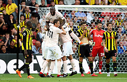 Manchester United's Chris Smalling (hidden) celebrates scoring his side's second goal of the game with team-mates Romelu Lukaku during the Premier League match at Vicarage Road, Watford