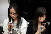 Junge Damen mit Mobil Telefonen in der Metro von Seoul.<br /> <br /> Young women with their mobile phones in the Seoul subway.