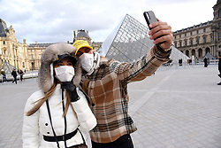 """Chinese tourists wear face mask as they take a selfie near the Louvre Museum in Paris, France, on January 28, 2020. An elderly Chinese tourist in a """"serious condition"""" in a Paris hospital is France's fourth confirmed case of the new coronavirus that has killed more than 100 people since it emerged in the Chinese city of Wuhan, France's top health official said Tuesday. Photo by Alain Apaydin/ABACAPRESS.COM"""