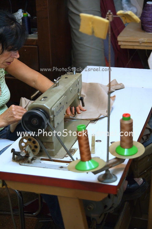 Woman sewing material on a machine in an  upholsterer workshop