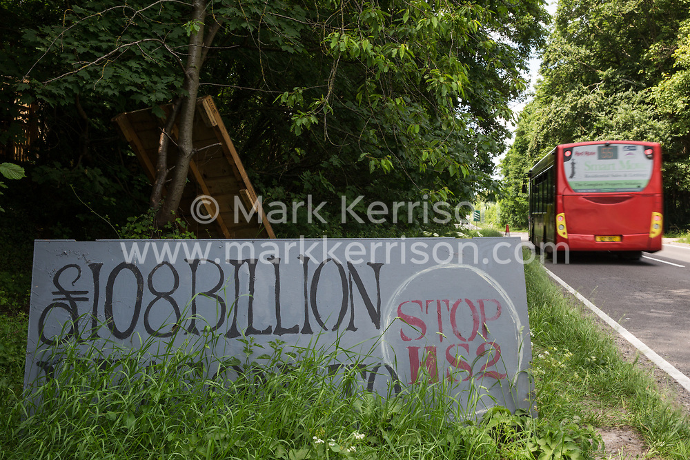 A painted sign criticising the cost of the HS2 high-speed rail link is pictured alongside the A413 outside Stop HS2's Wendover Active Resistance Camp on 16th June 2021 in Wendover, United Kingdom. Large areas of land around Wendover in the Chilterns AONB have already been cleared of trees and vegetation for the rail infrastructure project in spite of concerted opposition from local residents and environmental activists.