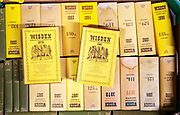 A box of Wisden Cricket almanack books on display in house clearance auction sale room, UK
