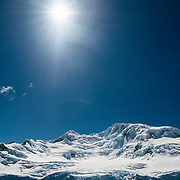 Snow-covered mountains in Antarctica against a deep blue sky with the sun.