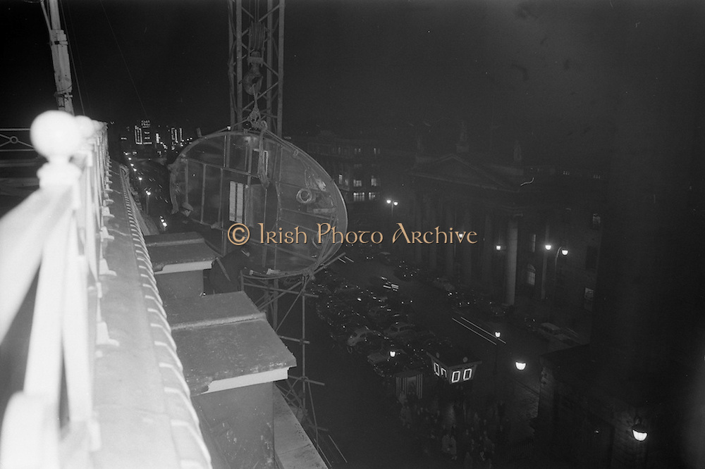 08/02/1963<br /> 02/08/1963<br /> 08 February 1963<br /> New Esso sign being erected at O'Connell Street Dublin. The sign being hoisted into place by crane, as workmen ease the sign into its new home.