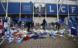 Volunteers relocate the tributes left for the victims of the Helicopter crash at the King Power Stadium, Leicester.