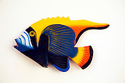 Carved wooden fish against white background