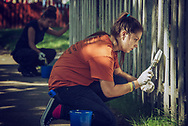 Young adult female kneeling outdoors painting a wooden fence with a paintbrush