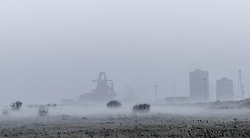 © Licensed to London News Pictures. <br /> 18/03/2015. <br /> <br /> Redcar, Teesside.<br /> <br /> Fog and mist descends across open ground in front of the steel works in an area known as South Gare near Redcar on Teesside.<br /> <br /> Photo credit : Ian Forsyth/LNP