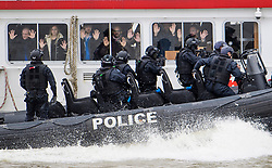 © Licensed to London News Pictures. 19/03/2017. London, UK. People playing hostages are seen holding up their hands as Anti-terror Police intercept a tourist boat, taken hostage by people playing armed terrorists, in an ant-terror training exercise takes place on The River Thames in  London. It is the first time that an exercise of this type has taken place on the river. Photo credit: Ben Cawthra/LNP