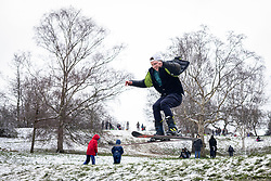 © Licensed to London News Pictures. 24/01/2021. London, UK. A skier performs a jump over a footpath as he skis down a hill in Greenwich Park in southeast London after snow fell over the capital. Photo credit: Rob Pinney/LNP